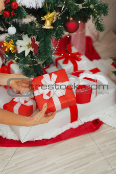 Closeup on woman hands putting Christmas present box under Christmas tree