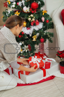 Woman putting Christmas present box under Christmas tree. Rear view