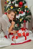 Woman putting present box under Christmas tree and showing shh gesture