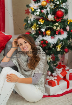 Happy young woman sitting near Christmas tree