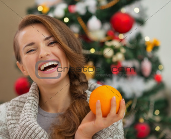Portrait of smiling young woman with orange near Christmas tree
