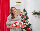 Portrait of happy woman with present boxes near Christmas tree