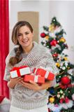 Portrait of smiling woman with present boxes near Christmas tree