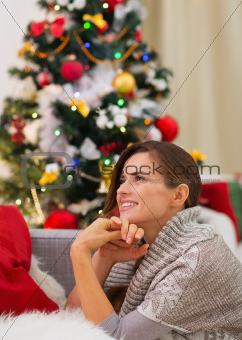 Dreaming young woman sitting near Christmas tree