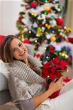 Smiling woman with Christmas rose sitting near Christmas tree