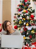 Thoughtful young woman with laptop sitting near Christmas tree