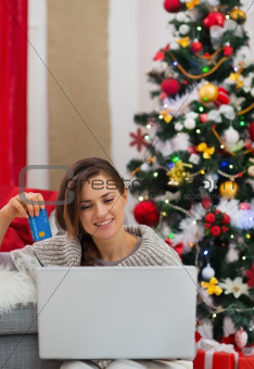 Smiling woman with laptop and credit card sitting near Christmas tree