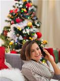 Happy young woman speaking mobile near Christmas tree