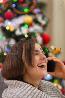 Portrait of smiling woman speaking mobile near Christmas tree