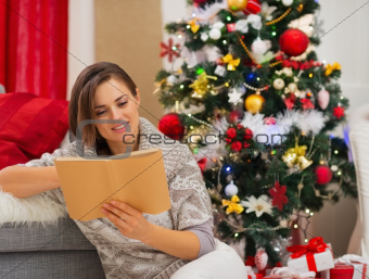 Young woman reading book near Christmas tree