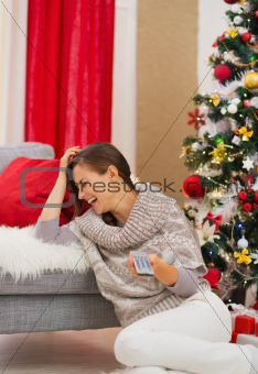 Laughing young woman watching TV near Christmas tree
