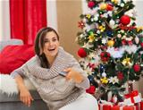 Surprised young woman watching TV near Christmas tree