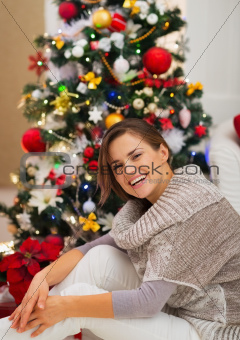 Portrait of happy young woman sitting near Christmas tree