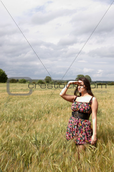 An attractive lady standing  in a field