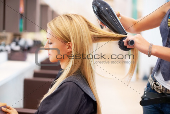 Getting her hair blow-dried by a professional