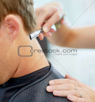 Cleaning up his hairline after a trim