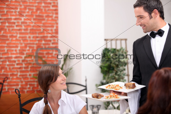 women at restaurant with waiter