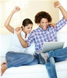 A young ethnic couple celebrating over something on the laptop