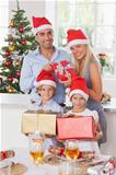 Family wearing santa hats holding christmas presents