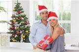 Happy couple holding a gift at christmas