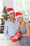 Attractive couple at christmas holding a gift