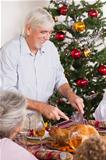 Grandfather carving turkey at christmas dinner