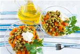 Salad with canned peas, boiled carrots and bottle oil on fabric