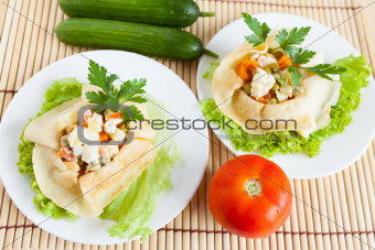 Two Salad with boiled vegetables wrapped in a pancake on a plate