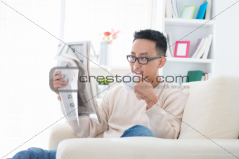 Asian drinking coffee and reading news paper