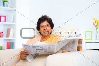 Mature Indian woman reading news paper