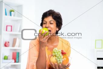 Mature Indian woman eating fruits