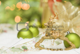 Beautiful Golden Christmas Reindeer Ornament Among Snow, Bulbs and Ribbon Against an Abstract Background.