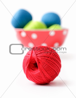 red ball of yarn for knitting in the background with the other b