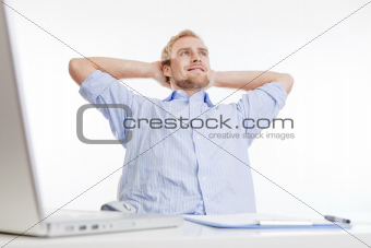 young man at office, sitting leaning back daydreaming, smiling