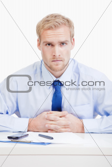 serious boss sitting behind desk at office looking at camera