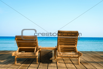 Two wooden beach chair, sea and clean sky