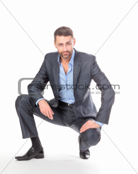 Portrait businessman sitting on his haunches