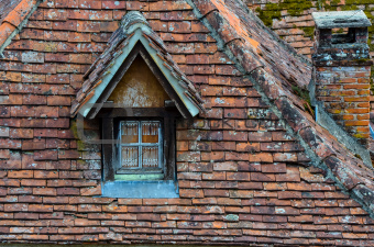 Old brick roof with window and a chimney