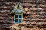 Old orange brick roof with broken glass winow