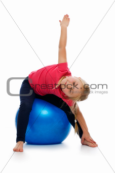 Little girl doing fitness exercise with gym ball.