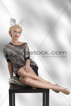 sexy girl with silver bunny ears looks in to the lens