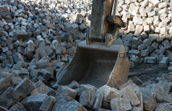 Grapple dredger scoops cobblestones.