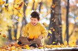Cute little boy painting with brush outdoors in park on beautiful autumn day