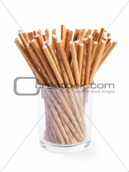 Glass with crispy sticks isolated on white