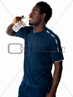 Tired african athlete drinking water