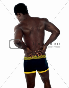 Back pose of young fit male trainer