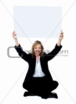 Seated female employee holding white clipboard over her head
