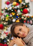 Portrait of dreaming young woman near Christmas tree