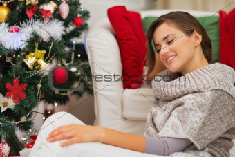 Portrait of calm young woman sitting near Christmas tree