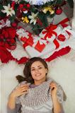 Portrait of happy young woman laying near Christmas tree